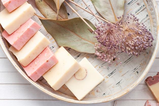 Barra di sapone naturale in un cestino di vimini sopra una priorità bassa di legno bianca e una decorazione secca delle foglie e dei fiori.