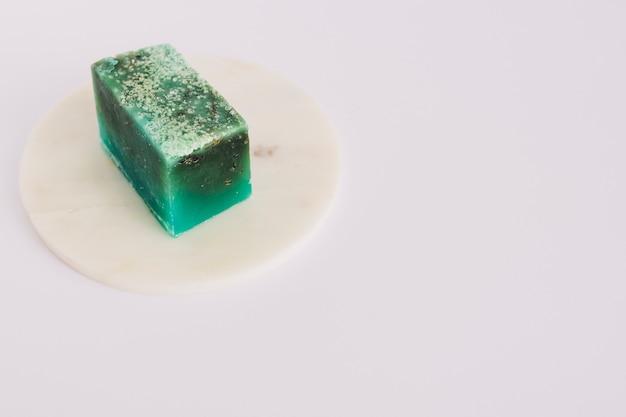 Barra di sapone verde sul bordo circolare sopra superficie bianca
