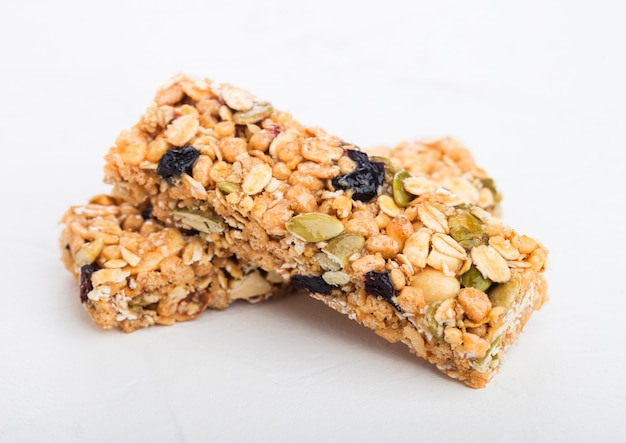 Barre di cereale organiche casalinghe del granola con le noci e la frutta secca su bianco.