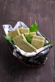 Barre di saponi naturali verdi dell'olio d'oliva con le foglie verdi in un canestro su di legno scuro