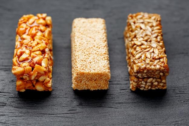 Barretta ai cereali con arachidi, sesamo e semi di girasole su un tagliere su un tavolo di pietra scura. vista dall'alto tre barre assortite