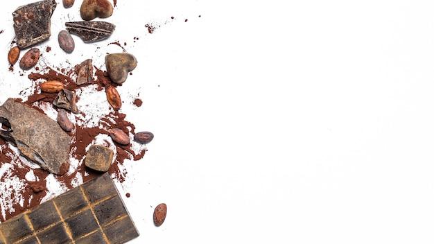 Barretta di cioccolato, fave di cacao, pezzi su uno sfondo bianco isolato.