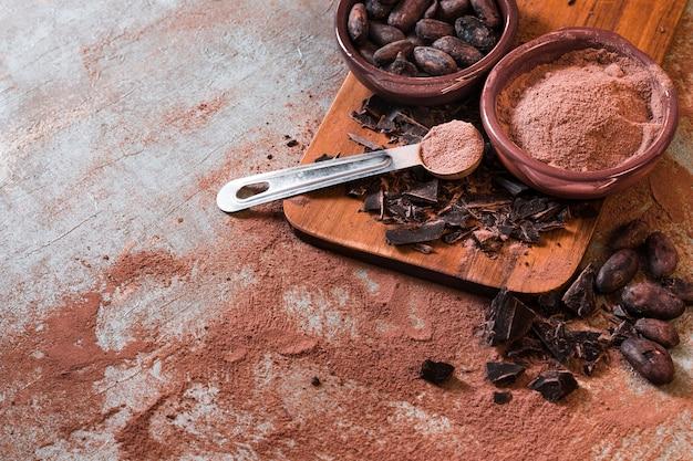 Barretta di cioccolato incrinata con polvere di cacao e fagioli