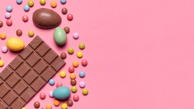 Barretta di cioccolato; uova di pasqua e caramelle gemma su sfondo rosa