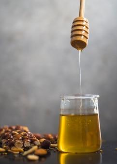 Barretta di muesli con miele che gocciola dalla caraffa di miele in vaso