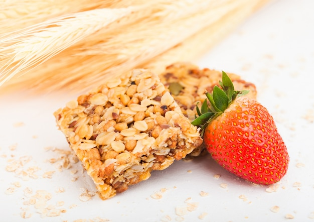 Barrette di cereali biologici fatti in casa granola con noci e frutta secca su bianco con avena e grano crudo e fragola