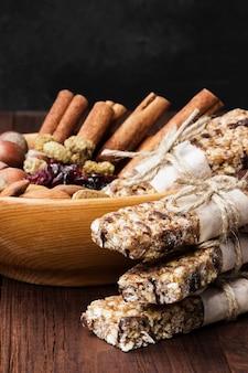 Barrette di cereali con diverse noci e muesli e ciotola di ingredienti