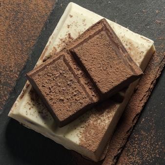Barrette di cioccolato bianco e fondente impilate su fondo di pietra grezza nera ricoperta di cacao in polvere