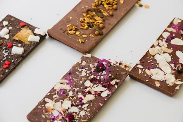Barrette di cioccolato con diversi condimenti su sfondo bianco