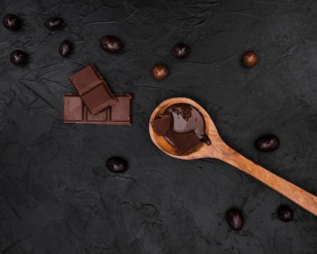 Barrette di cioccolato e cucchiaio di legno con sciroppo di cioccolato