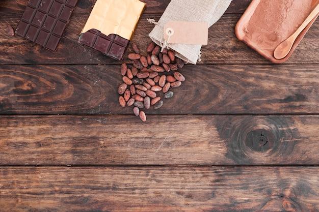 Barrette di cioccolato, fave di cacao e polvere sulla scrivania di legno