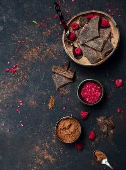 Barrette di cioccolato nero e un lampone sublimato come decorazione nel piatto di cocco.