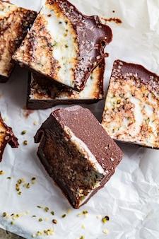 Barrette di cioccolato vegano crudo con noci e semi, vista dall'alto. dessert salutare senza zucchero.