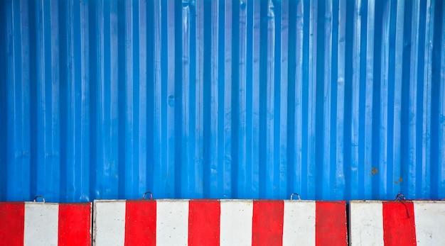 Barriere di cemento rosso e bianco che bloccano la strada davanti a un contenitore blu