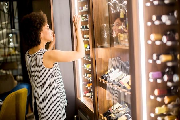 Basamenti della giovane donna che osservano bottiglia di vino