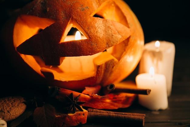 Basamento della zucca di halloween di scarry sulla tabella con le candele e la cannella