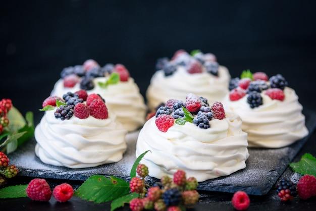 Base di meringa fatta in casa per torta pavlova con mirtilli freschi e mora e zucchero a velo su cemento nero