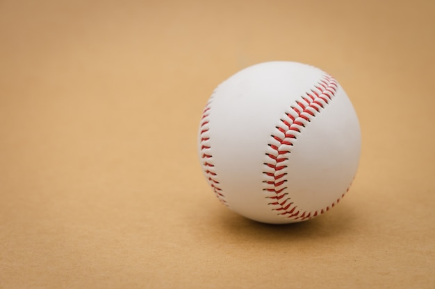 Baseball isolato su una priorità bassa marrone e un baseball di cucitura rosso. baseball bianco