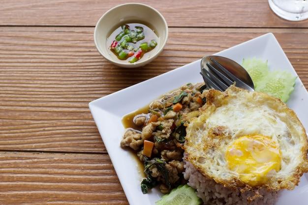 Basil fried chicken e uovo fritto sul tavolo di legno