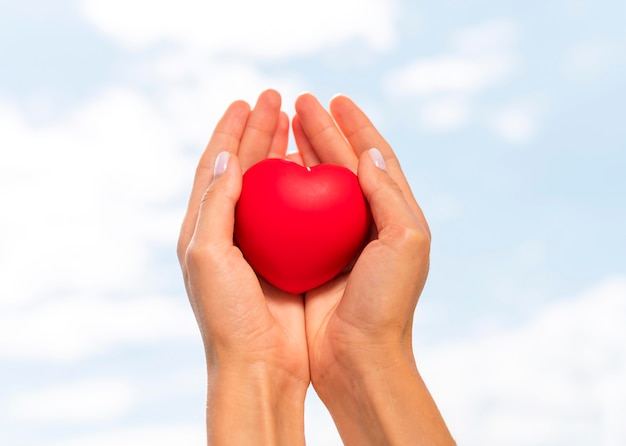 Basso angolo di mani che tengono a forma di cuore con il cielo