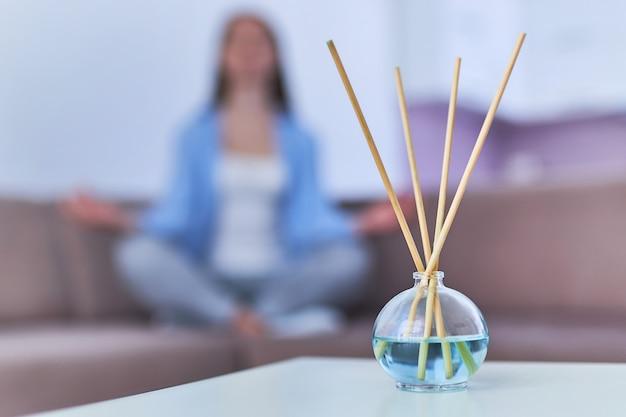 Bastoncini aromatici e bottiglia di olio essenziale per il relax, la meditazione e la salute mentale