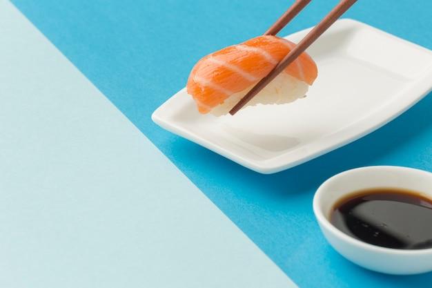 Bastoncini del primo piano che tengono i sushi