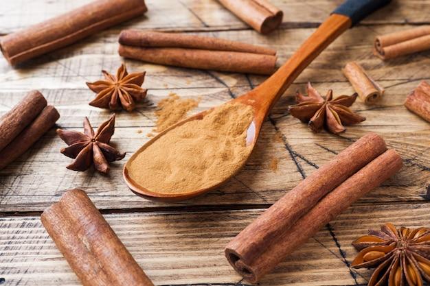 Bastoncini di cannella e terra fragranti delle spezie, anice stellato su di legno.
