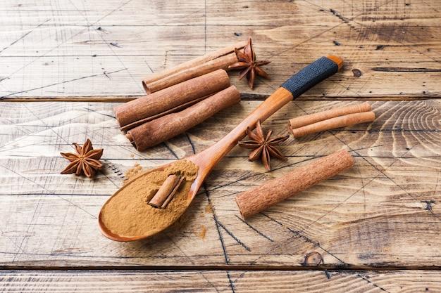 Bastoncini di cannella fragranti spezie e terra, anice stellato su fondo di legno.