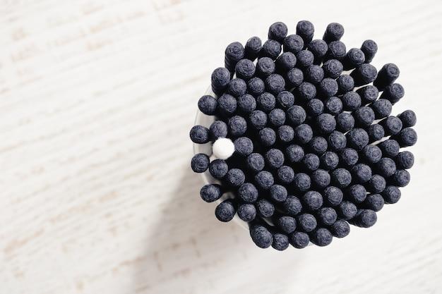 Bastoncini di cotone neri con un singolo bastoncino di cotone bianco tra loro visti dall'alto. concetto di diversità