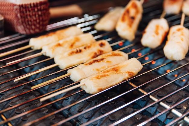 Bastoncini di formaggio alla griglia sulla stufa a gas, cibo di strada a ximending a taiwan, taipei.