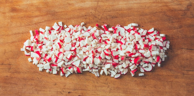 Bastoncini di granchio tritati finemente sul tagliere.