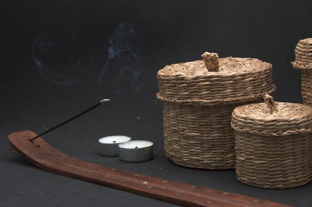 Bastoncini di incenso, candele e cestini di paglia su sfondo nero.
