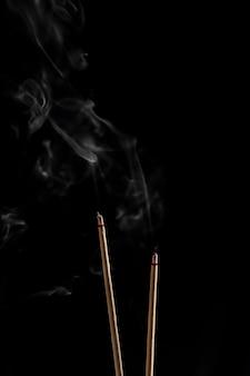 Bastoncini di incenso e bastoncini di incenso fumo su backgrond nero