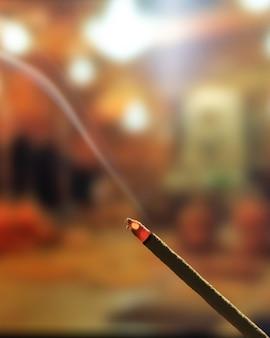 Bastoncini di incenso in fiamme con fumo, bastoncini d'incenso che bruciano in un tempio buddista vintage