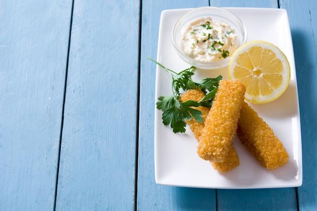 Bastoncini di pesce fritti croccanti con il limone e la salsa su di legno blu, copi lo spazio