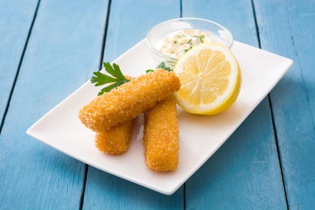 Bastoncini di pesce fritti croccanti con il limone e la salsa su legno blu