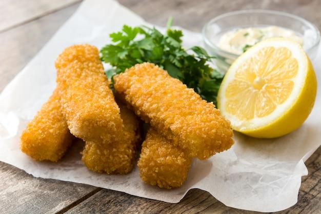 Bastoncini di pesce fritti croccanti con il limone e la salsa su legno