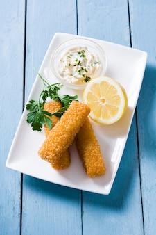 Bastoncini di pesce fritti croccanti con il limone e la salsa sulla vista di legno e superiore blu