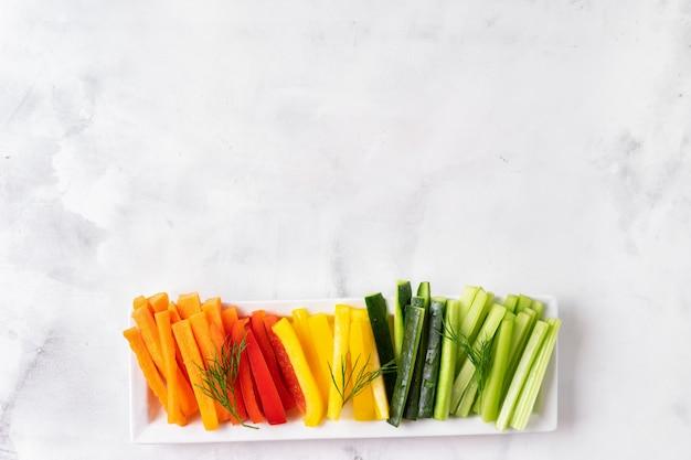 Bastoncini di verdure colorate nel piatto lungo. vista dall'alto.