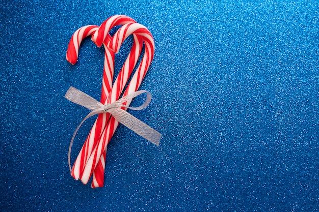 Bastoncini di zucchero con fiocco d'argento su sfondo blu glitter per biglietto di auguri di natale e