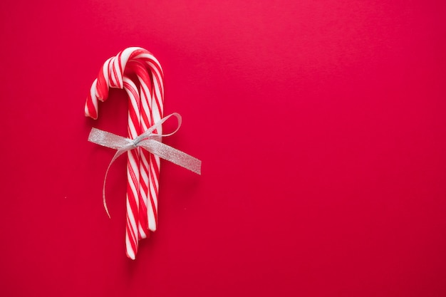 Bastoncini di zucchero con fiocco d'argento su sfondo rosso per biglietto di auguri a natale e capodanno