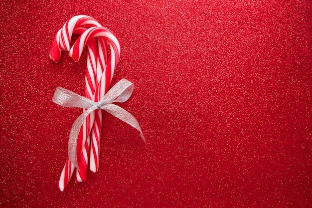 Bastoncini di zucchero con fiocco in argento su sfondo rosso glitter per biglietto di auguri su natale e n