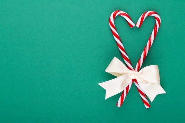 Bastoncini di zucchero di natale, bastone e decorazioni su sfondo colorato. sweet christmas card - bastoncini di zucchero con nastro - immagine.