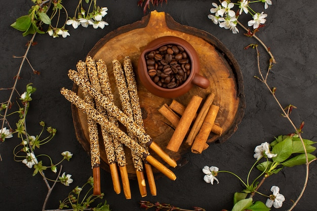 Bastoncini di zucchero vista dall'alto insieme a semi di caffè marrone e cannella sul pavimento scuro