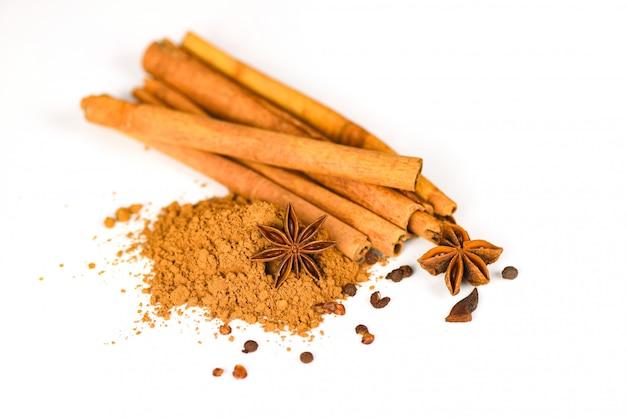 Bastoncini e anice stellato di cannella sulle erbe e sulle spezie della polvere di cannella su bianco