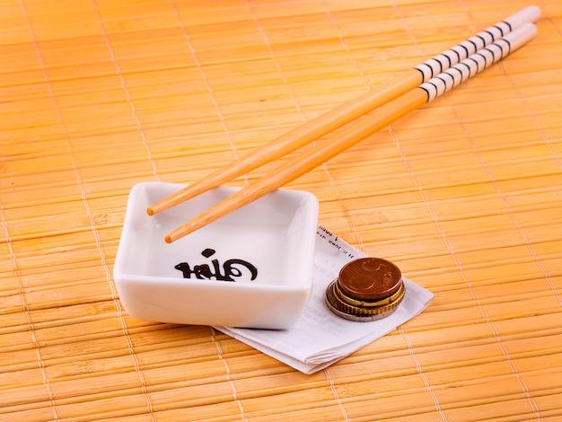 Bastoncini e una tazza per sushi con un assegno e l'euro.