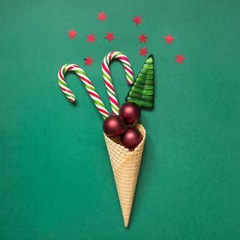Bastoncino di zucchero di natale, palle rosse in cono gelato su verde.