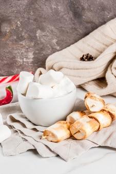 Bastoncino di zucchero, marshmallow e spiedini di marshmallow al forno su sfondo bianco