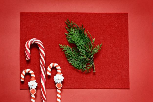 Bastoncino di zucchero su uno sfondo rosso con un rametto di abete