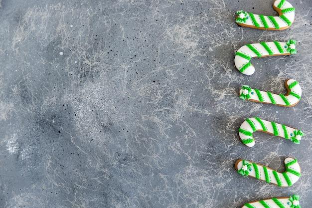 Bastoncino di zucchero verde e bianco del pan di zenzero dipinto a mano di natale su un bello fondo grigio.